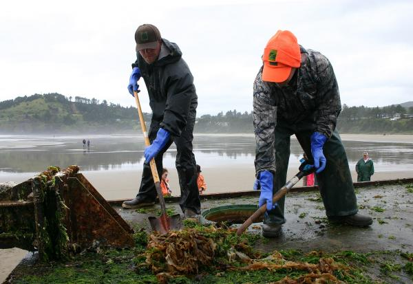 Workers scrape invasive species off of the derelict dock. Courtesy of Oregon Parks and Recreation Dept.""