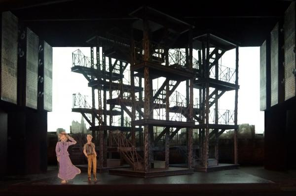 The mobile metal scaffoldings in Ost's design stand in for the cityscape and also support screens for the production's video projections.