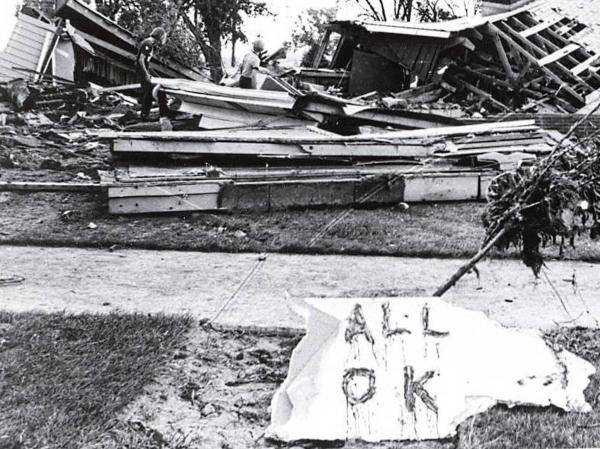 "Two children climb over what remains of a home that has an ""All OK"" sign in front. The flood caused $165 million of damage to the area."
