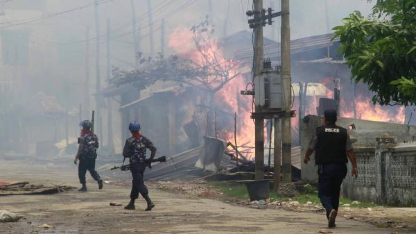 Policemen walk toward burning buildings in Sittwe, where some residents fled burning homes and gunshots as deadly ethnic violence broke out.