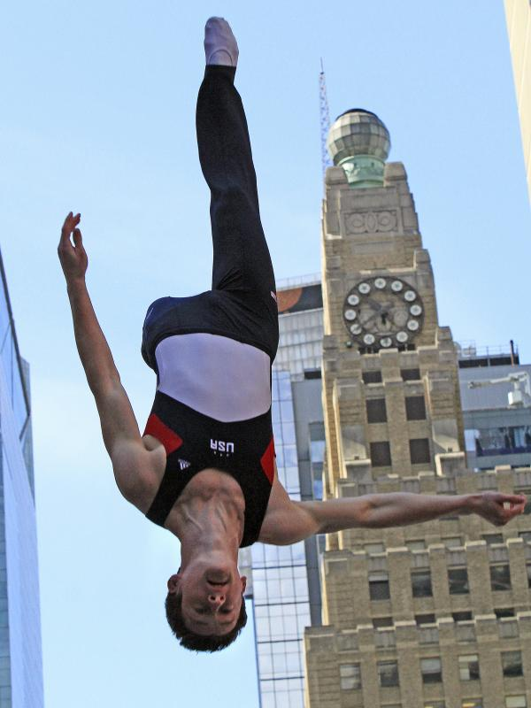 Jeffrey Gluckstein goes upside down on a trampoline in New York's Times Square during U.S. Olympic team festivities.