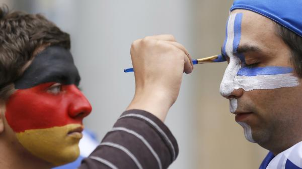 An artist with the German national colors on his face paints the Greek colors on a soccer fan in Gdansk, Poland, on Friday as Germany and Greece prepared to play in the quarterfinals of the Euro 2012 soccer championship.
