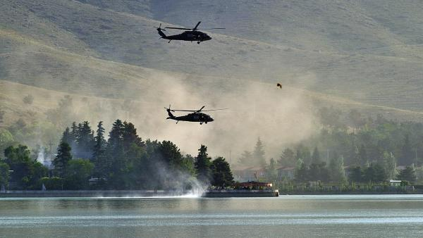Responding to a Taliban attack, NATO Black Hawk helicopters fly over the Spozhmai Hotel on Lake Qargha outside Kabul. More than 20 people were killed before the Taliban fighters were shot dead.