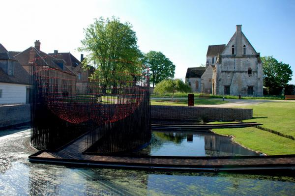 Andy Cao and Xavier Perrot's <em>Red Bowl </em>installation in Beauvais, France, allows visitors to cross a pond into a hemisphere of metal rods topped with red marbles.