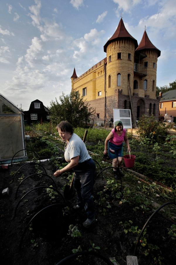 In the mishmash of a dacha community, an ersatz schloss and wooden shack may stand shoulder to shoulder. Here, Zinaida Kondratyeva, owner of the modest wood house in the background, works with her daughter-in-law in her garden near Moscow. The castle-like house is owned by a lawyer.