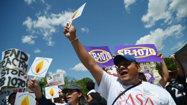Protesters outside the U.S. Supreme Court shout slogans during an April 25 protest against Arizona Senate Bill 1070.
