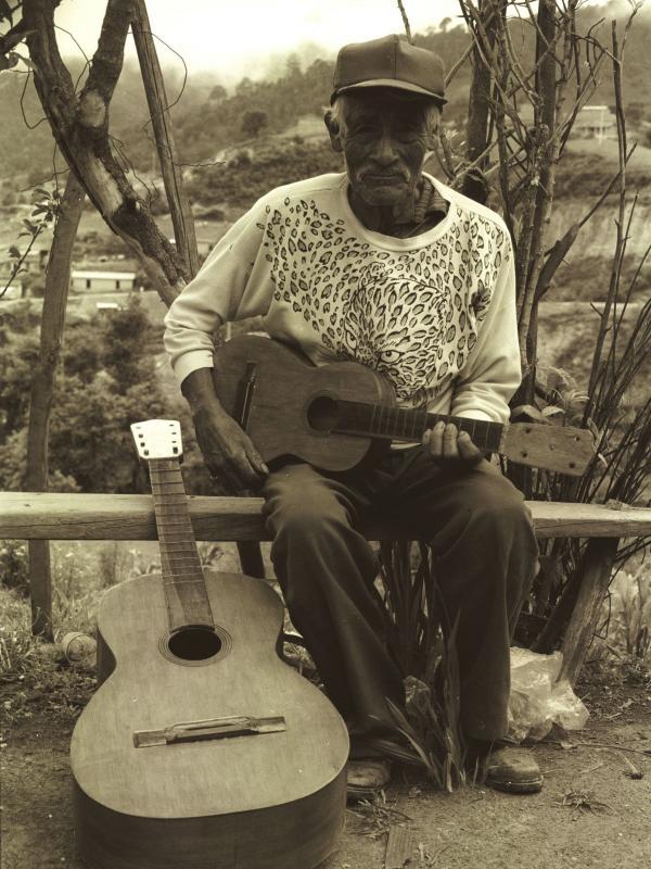 Don Telesforo next to a bajo quinto, holding a jarana mixteca.