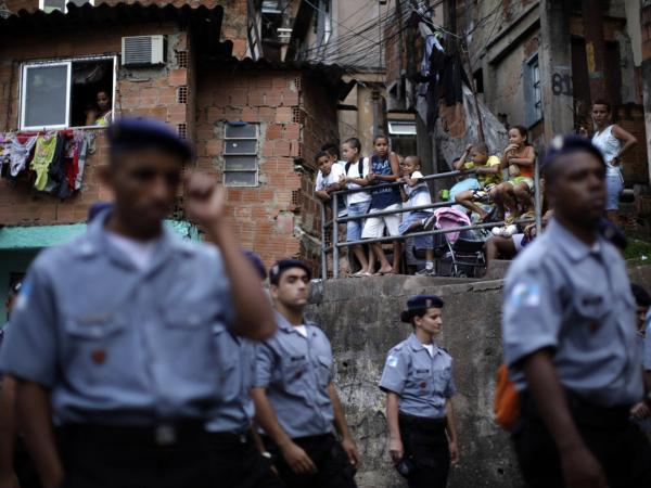 <p>Police officers of the Peacemaker Police Unit program, UPP, patrol the Morro dos Macacos slum last year. The city has stepped up efforts at community policing in order to rid the <em>favelas</em> of drug traffickers.</p>