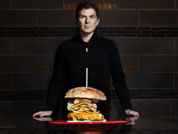 <p>Bobby Flay pictured with a cheeseburger</p>