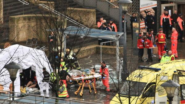 Rescuers evacuate injured people in Liege, Belgium, today, after a grenade and gun attack that killed at least three and injured dozens.