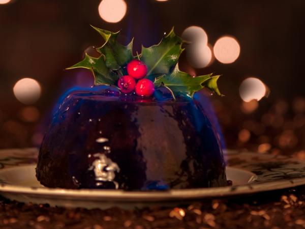 The pudding's dark glossy dome is  flamed with brandy and carried to the table before the shimmering blue aura dies away.