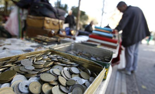 Old drachma coins are displayed for sale at an outdoor market in Athens. If the international community concludes that Greece can't be saved as a member of the Eurozone it will have to revert to its old currency.