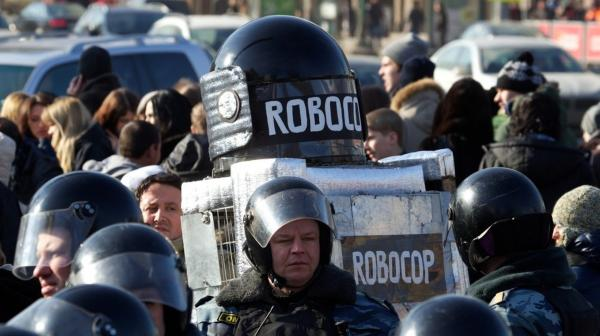 A protester wearing a costume bearing the words Robocop walks among Russian riot police officers after a rally in Moscow on Saturday.