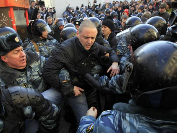 Police officers detain opposition leader Sergei Udaltsov after the rally Saturday.
