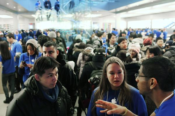 People speak to Apple employees as they wait in line to purchase the new iPad which went on sale around the world on Friday.