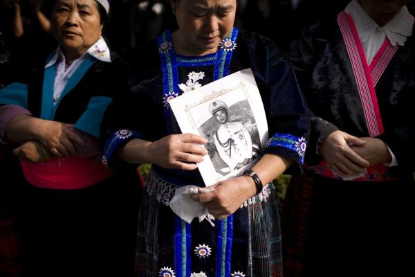 A mourner holds a photo of  Gen. Vang Pao during the funeral procession. Vang was a hero of the Hmong community, and thousands gathered for his six-day long funeral. He died on Jan. 6 at age 81.