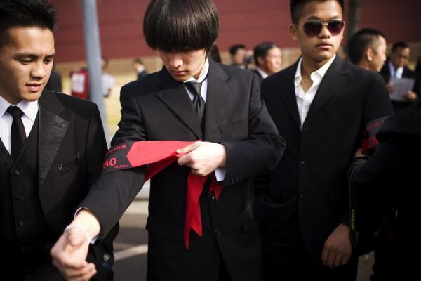 Kingsley Yang ties on an armband during the funeral procession. Members of the general's family had hoped he would be buried in Arlington National Cemetery, but the Pentagon denied the request.