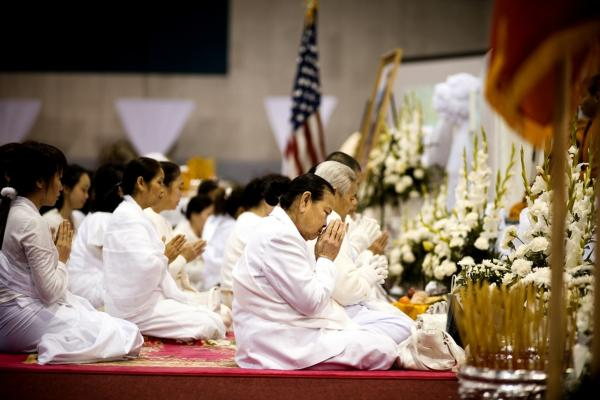 Family members pray during the Buddhist ceremony for Vang. The six-day funeral ended on Feb. 9.