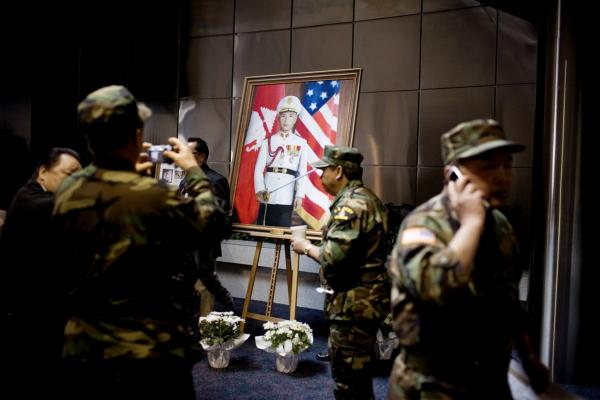 Former U.S. soldiers surround a portrait of Gen. Vang Pao.  They were among the thousands attending the general's funeral.