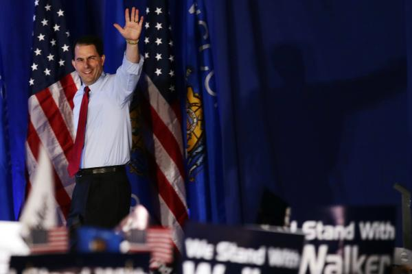 Wisconsin Gov. Scott Walker waves at his victory party Tuesday in Waukesha, Wis. The Republican survived a recall election in the state, defeating his Democratic rival, Tom Barrett.