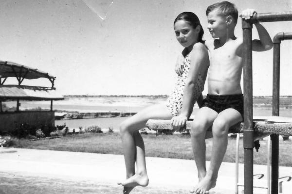 Children sit on the diving board at the community pool. It was the country's only co-ed pool.