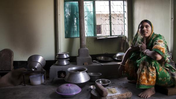 A woman at home in Bangladesh with an improved cookstove