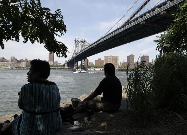 Gloria and Daniel Perez sit in a shady spot near the Brooklyn side of the Manhattan Bridge trying to beat the weather during a days-long heat wave of temperatures above 90 degrees.