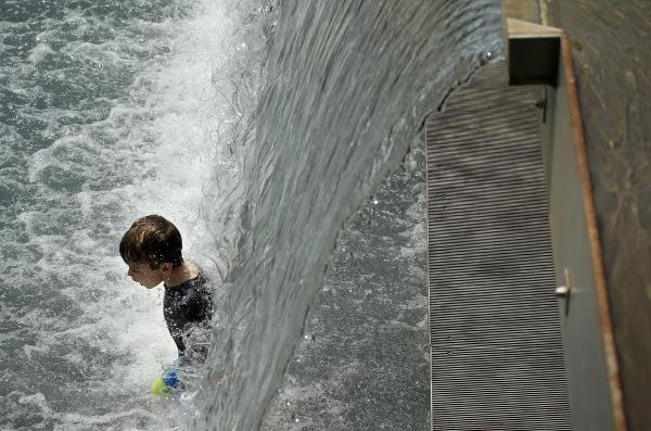 A child plays in a fountain at the Yards Park in Washington, D.C. Forecasters predict the record heat wave in the area will last through Sunday, with daily triple-digit temperatures.