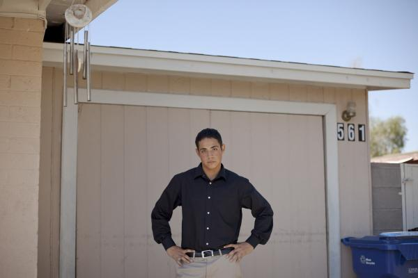 Luis de la Cruz stands in front of the garage where he lived without air conditioning near Phoenix. He lived there with his brother while finishing high school after his father was deported and his mother abandoned them. He is now an honors student at Arizona State University.