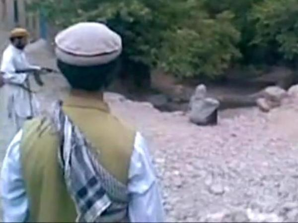 A screen grab from the video of a public execution reportedly carried out last month in Afghanistan. The victim is sitting with her back to the executioner, who is at left.