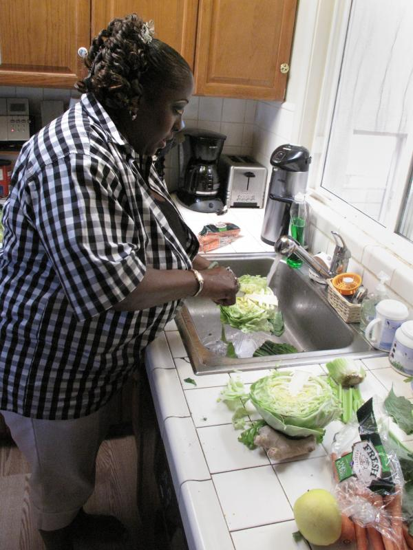 Yovanda Dixon washes vegetables in her San Francisco home to prepare a demonstration for her support group.