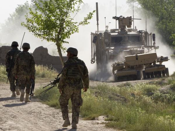 Afghan soldiers walk toward a U.S. Army mine-sweeping vehicle in southern Afghanistan on June 10. Roadside bombs remain a major threat to U.S. and Afghan troops, as well as civilians.