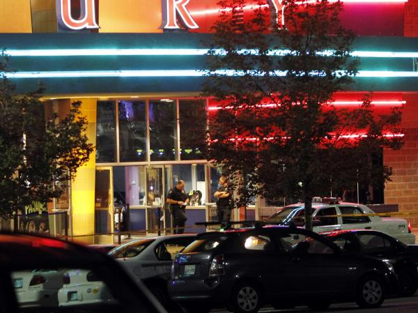 A police officer outside the Century 16 movie theater in Aurora, Colo., early Friday after a gunman opened fire on people watching a midnight screening of <em>The Dark Knight Rises</em>.