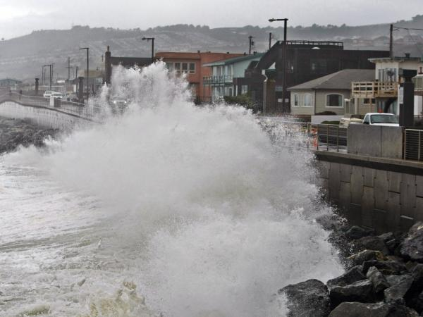 Waves pound a sea wall in Pacifica, Calif., during a storm in 2010. Small assumptions can make a big difference when putting a price-tag on future disasters.