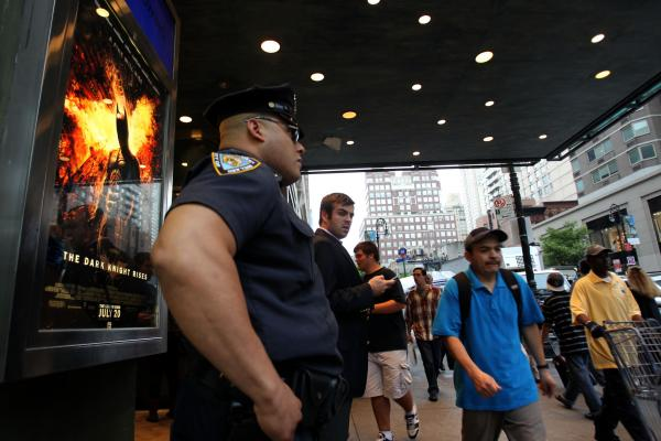 "A policeman stands outside a movie theater in New York on Friday during a showing of ""The Dark Knight Rises."""