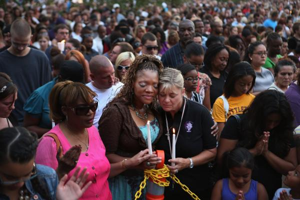 Titia Stillwell and Lori Meade embrace and pray with thousands of others during Sunday's vigil.