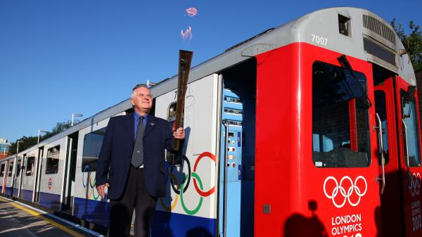 London Underground employee John Light (!) carries the Olympic torch onto a train at Wimbledon Station.