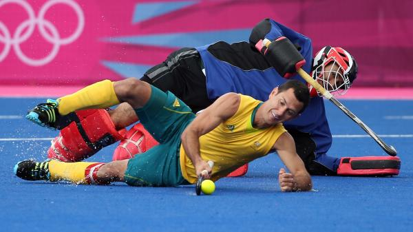 Australia's Jamie Dwyer, who scored three goals against South Africa in field hockey Monday, goes horizontal in London's Riverbank Arena. The South African goalie matched Dwyer's strategy, but Australia won, 6-0.