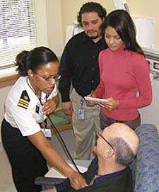 A clinical nurse conducts an examination with the help of two interpreters. Photo courtesy NIH