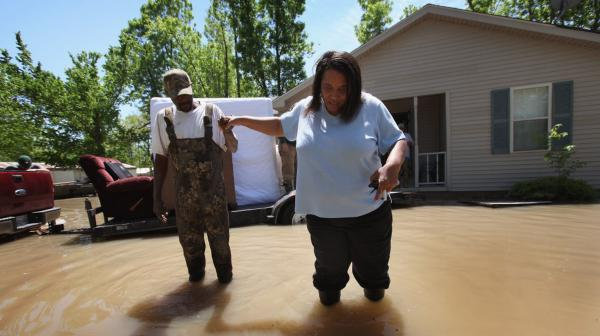 Will Swift helped Oma Gardner from her flooded home in the town of Tiptonville, Tenn. Heavy rains have left the ground saturated, rivers swollen, and has caused widespread flooding from Illinois to Arkansas.