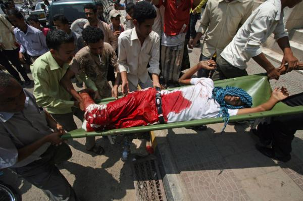 Protestors carry a wounded protester from the site of clashes with security forces, in Taiz, Yemen on Monday.