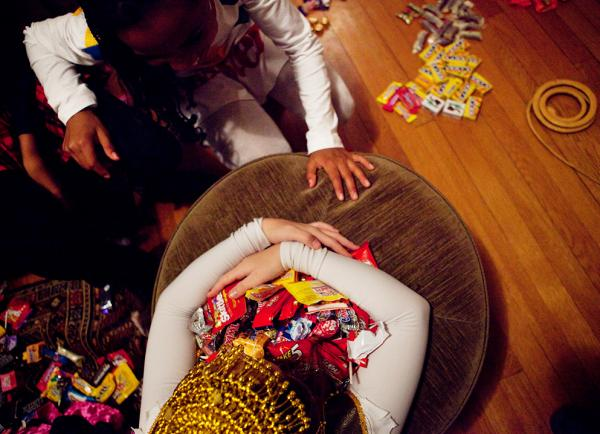 <p>Eden Rose Breslow grabs her loot as Sierra Lewter goes in for a trade after trick-or-treating on Monday. </p>