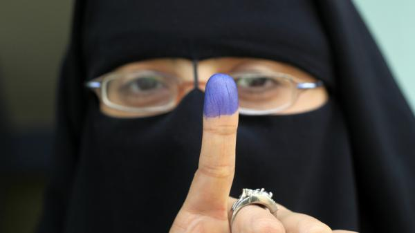 An Egyptian woman shows her ink-stained finger after voting at a polling station in the Manial neighborhood of Cairo earlier today (Nov. 28, 2011).
