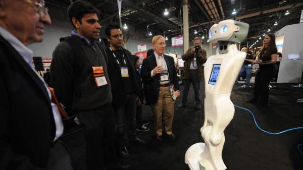 The QA telepresence robot by Anybots chats with people on the floor at the Consumer Electronics Show in Las Vegas in January 2009. The CEO of one Silicon Valley startup uses an Anybots robot around the office when he's away on business.