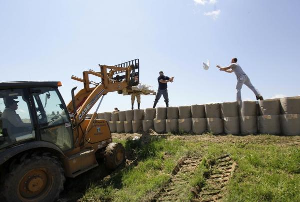 April 28: Workers toss sandbags atop the flood wall they are building to protect Smithland, Ky. from the rising Ohio River.