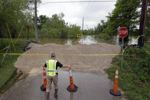 April 26: Detective Corey Mitchell adjusts traffic cones near a temporary levee holding back water from the Black River in Poplar Bluff, Mo.