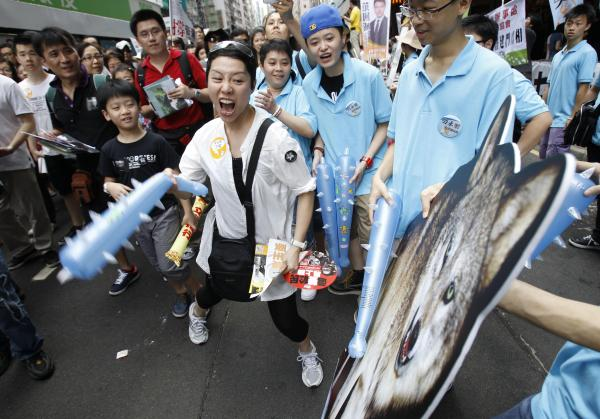 A protester hits a picture of a wolf representing Leung Chun-ying during a pro-democracy protest march in Hong Kong on Sunday, the anniversary of the island's handover to China. There is rising public discontent over widening inequality and a lack of full democracy in the southern Chinese financial center.