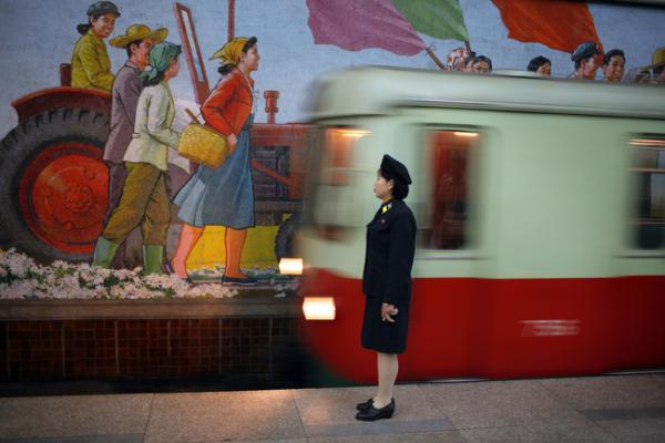 An attendant stands near the tracks as a metro train arrives in Pyongyang, North Korea, August 2007.