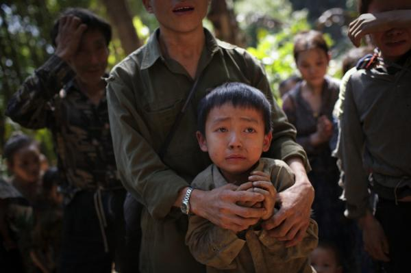 Hmong villagers break down in tears at their hidden village in Laos, November 2007. The villagers are regular targets of the Lao People's Army for their roles in collaborating with the CIA during the Vietnam War. Their families have had limited contact with Westerners since 1975.