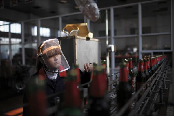 A worker inspects labels on beer bottles as they move down the production line at a brewery in Nanjie village, Henan province, China, November 2009. Nanjie is a collective village run along Maoist lines. Residents have socialist benefits like free education and health care, but there is no private property.